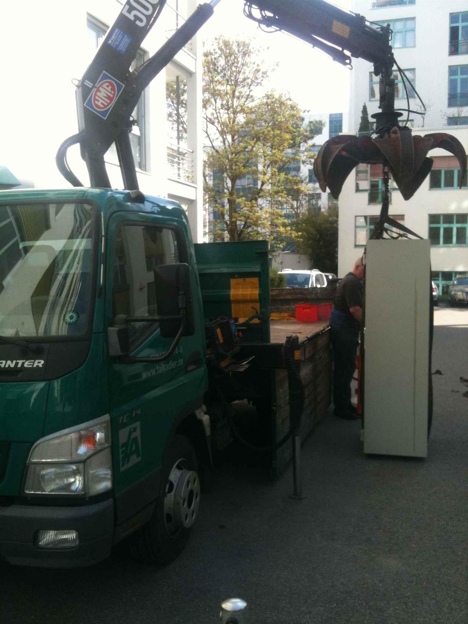 LKW mit Kran. Tresor wird aufgeladen